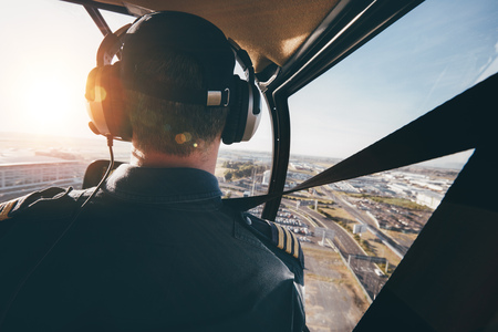 helicopter pilot: Rear view of a male wearing headphones flying a helicopter. Pilot flying an aircraft over a city.