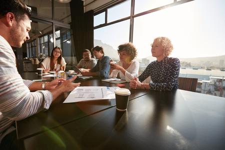 Portrét tvůrčího týmu sedí kolem stolu diskutovat o nových projektových záměrů. Smíšené rasy lidé setkání v kanceláři.