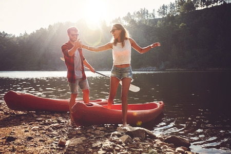 Young man helping woman to step out of a kayak. Couple after kayaking in the lake on a sunny day. Stock Photo