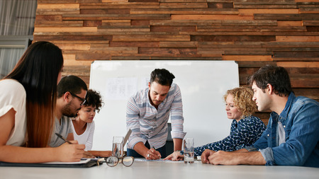 real leader: Group of colleagues having a brainstorming session in conference room. Young man explaining business plans to coworkers during meeting in boardroom.