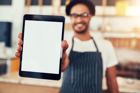 빈 디스플레이 태블릿 컴퓨터를 들고 웨이터의 초상화를 닫습니다. 디지털 태블릿을 보여주는 커피 숍 소유자입니다. 스톡 콘텐츠