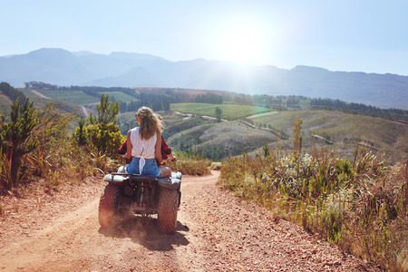 quad: Rear view shot of young woman sitting behind her boyfriend driving a quad bike on a sunny day. Couple in countryside riding on an ATV. Stock Photo