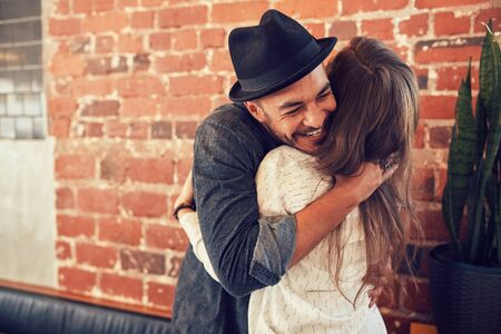 Portrait of young man embracing his girlfriend at cafe. Young man hugging a woman in a coffee shop.