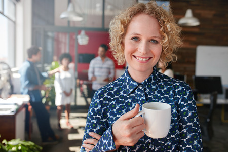 Portrait of happy young businesswoman holding a cup of coffee looking at camera and smiling. She is standing in her office with team of colleagues talking in background. Stock Photo