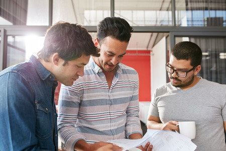Creative team working on their business project together at office. Three young men looking at some documents in a small meeting.