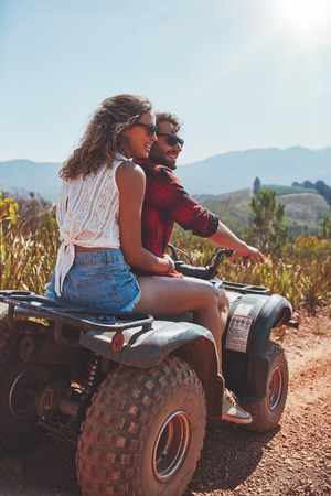carefree: Portrait of young man and woman in nature on a off road vehicle. Young couple enjoying a quad bike ride in countryside.