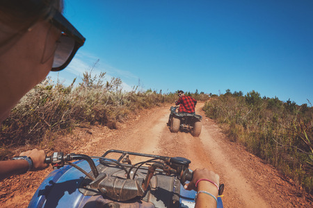 quad: Young people driving quad bikes with man in front . Man and woman on country ride on an all terrain vehicle.
