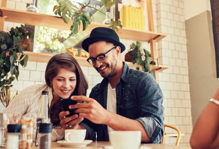 Portret van jonge vrienden zitten in een cafe te kijken naar de foto's op de mobiele telefoon. Gelukkige jonge mensen bijeen in een restaurant met behulp van mobiele telefoon. Stockfoto