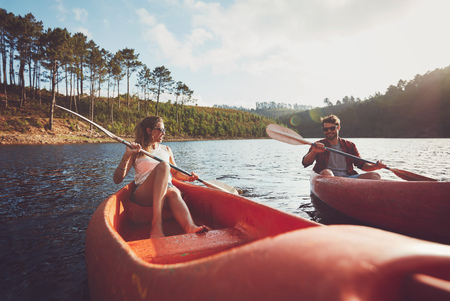 outdoor pursuit: Young couple kayaking on a lake. Young kayakers rowing on lake on summer day. Stock Photo