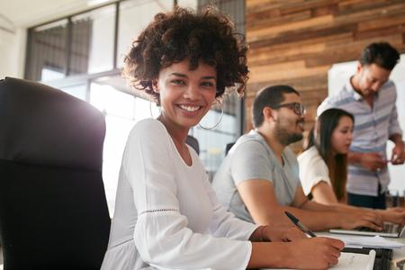 razas de personas: Retrato de mujer joven y atractiva que se sienta en sala de conferencias con colegas en segundo plano.