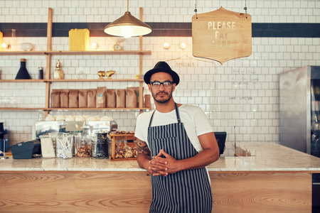 Portrait of a confident young coffee shop owner standing at the cafe counter. Handsome young man working at a restaurant and wearing an apron and hat. Stock Photo