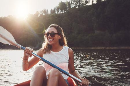 sonrisa: La mujer joven sonriente kayak en un lago. Mujer joven feliz en canoa en un lago en un d�a de verano.