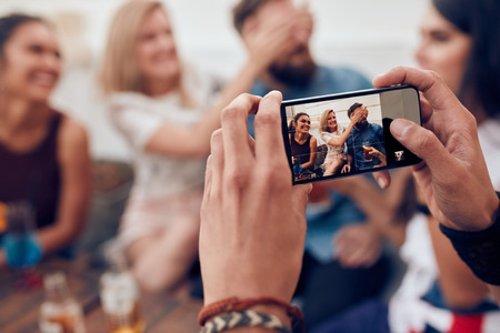 Photographing a group of friends with mobile phone. Young people having fun at a party.