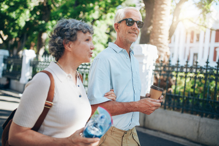 tourists: Senior man and woman walking in the city. Mature tourist roaming in a town during their vacation.