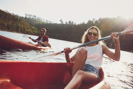 美しい若い女性がバック グラウンドでパドリングの男と湖でカヤックします。夏の日のカヌー若いカップル。