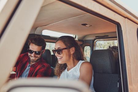 Pareja joven sentado en su coche durante el recorrido. Hombre joven y mujer que llevaba gafas de sol sentado en el interior del coche y sonriente. Foto de archivo