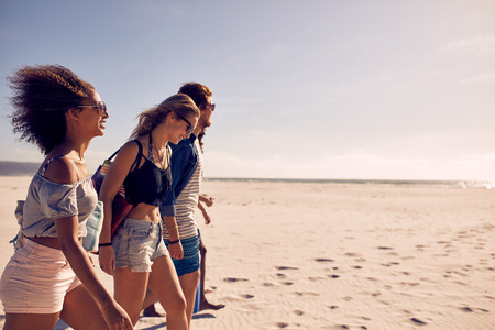 Portrait of young people walking along the beach on a summer day. Men and women on the sea shore. Group of friends on the beach together.