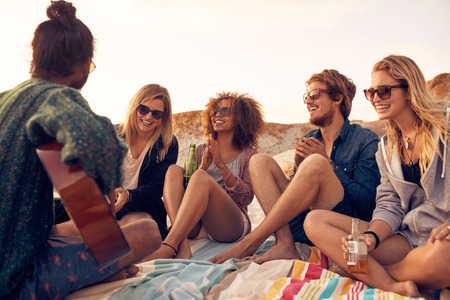 Group of young people listening to friend playing guitar outdoors. Diverse group of friends hanging out at beach. Young men and women drinking beers and enjoying music. Stock Photo