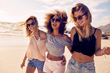 해변에서 산책 아름 다운 젊은 여자의 그룹입니다. 세 친구가 해변에 산책과 여름 날에 웃으면 서 휴가를 즐기는.