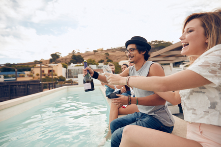 swimming pool woman: Outdoor shot of happy young people sitting on the edge of the pool drinking champagne. Multiracial friends enjoying and toasting drinks during a rooftop party.