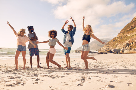 Multi-ethnic group of friends together on the beach having fun. Happy young people dancing on the beach. Group of friends enjoying summer vacation on a beach. Imagens
