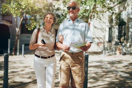 roaming: Senior couple walking around the city holding a map. Mature couple with a map roaming around the city.