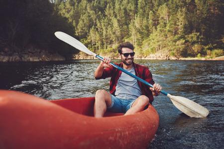 Jonge man kajakken op een meer. Gelukkig jonge man kanoën in een meer.