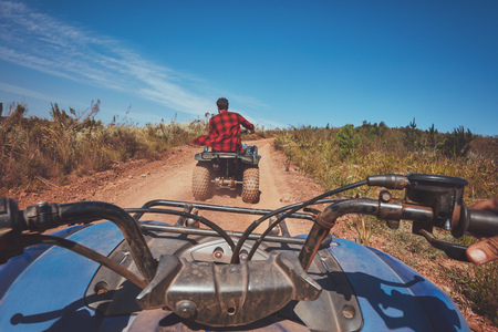 atv: View from a quad bike in nature. Man in front driving off road on an all terrain vehicle. POV shot. Stock Photo