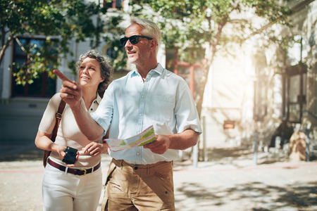 family vacation: Mature couple tourist exploring a foreign city. Senior couple using map and looking for the direction. Stock Photo