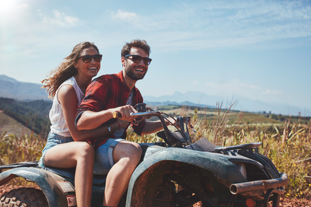 country roads: Portrait of loving young couple cruising over country roads by quad vehicle. Happy man and woman driving a quad bike.