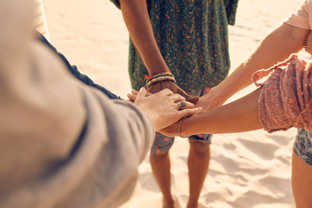 multiracial: Friends at the beach putting hands together. Multiracial group of young people with hands in stack at the beach. Stock Photo