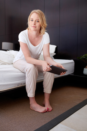 beautiful mature woman: Portrait of beautiful mature woman sitting on bed holding a digital tablet at home in bedroom.