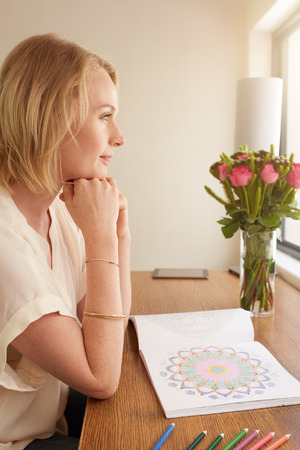 side table: Side view of thoughtful mature woman sitting at a table with adult coloring book and pencils colors.