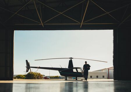 helicopter pilot: Silhouette of a pilot walking in hangar with a parked helicopter. Pilot arriving at the airport with a helicopter in background. Stock Photo