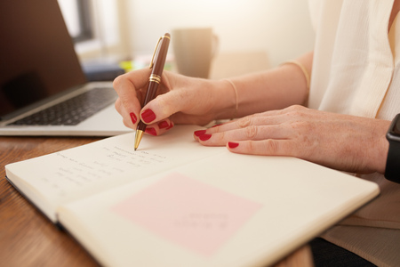 business lifestyle: Close up image of woman writing notes in her diary. Businesswoman sitting at her desk and taking important notes in her personal organizer.