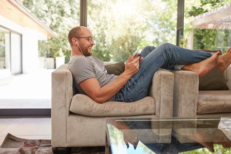 使用數字平板電腦,而坐在家裡的沙發上一個幸福的成熟男子的側面圖像。白人男子放鬆沙發上看著平板電腦和微笑。 版權商用圖片