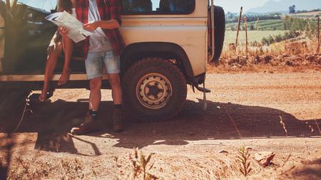 道路の旅地図とカップルのショットをトリミングしました。若い男と女・ カー田舎道で停止して道順の地図を読みます。 写真素材
