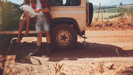 Cropped shot of couple with a map on road trip. Young man and woman with car stopping by a country road and reading map for directions. Reklamní fotografie