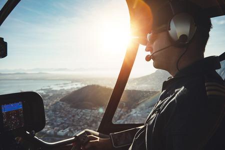 Close-up van een mannelijke piloot vliegt een helikopter over de stad van Kaapstad op zonnige dag