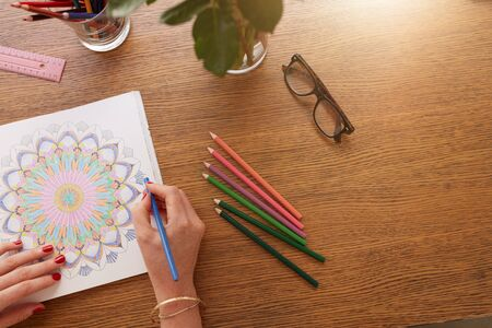 female hands: Close up image of female hands drawing in adult colouring book on a table at home. Stock Photo