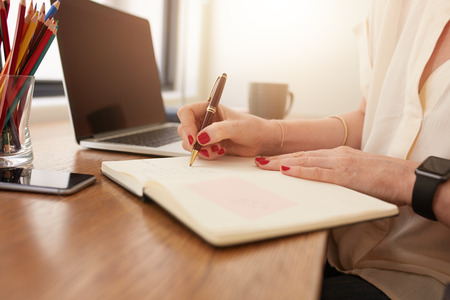 writing desk: Close up image of woman sitting at her desk and writing notes. Businesswoman working at home office. Stock Photo
