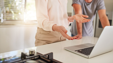 home office: Cropped shot of couple working together on a laptop in the kitchen. Couple standing by the kitchen counter, with woman explaining business proposal to man. Stock Photo
