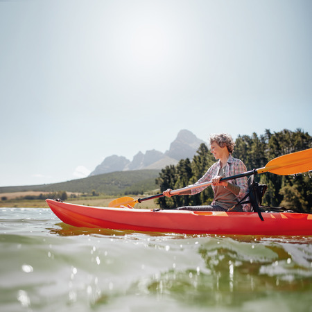 Portrait of a mature woman with kayak in a lake. Senior woman paddling kayak on a summer day. Reklamní fotografie