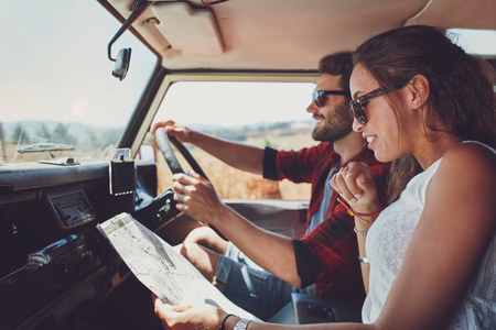 Side view of young couple using a map on a roadtrip for directions. Young man and woman reading a map while sitting in a car. Stock Photo
