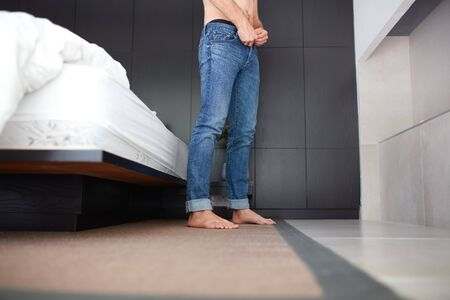 Low angle shot of a young man putting his jeans, he is standing by the bed in bedroom. Stock Photo