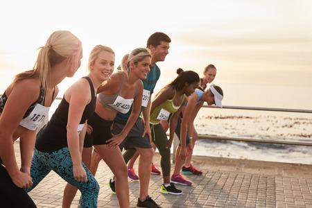 El inicio de un maratón, los atletas de pie en la línea de salida. Ejecución de la competencia en el paseo marítimo.