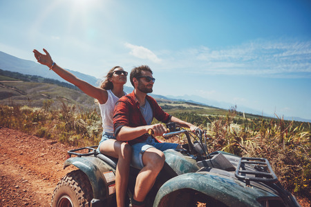 quad: Happy young couple in nature on a quad bike. Young man and woman enjoying a quad bike ride in countryside. Man driving and woman enjoying the ride with her hands raised on a summer day.