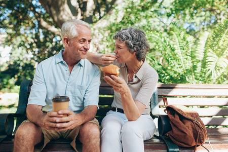 scene season: Loving senior couple sitting on a park bench having coffee and muffins. Tourist relaxing outdoors on a park bench.