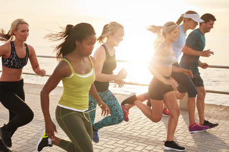 sports: Portrait of healthy young men and women running race on seaside promenade. Group of young people sprinting outdoors at sunset.