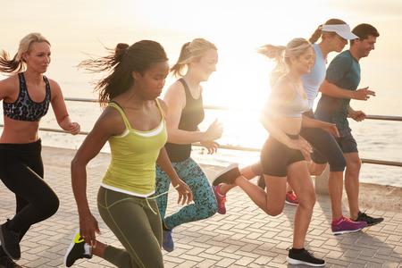 Portret zdrowych, młodych mężczyzn i kobiet prowadzących wyścig na nadmorskiej promenadzie. Grupa młodych ludzi sprint na zewnątrz o zachodzie słońca. Zdjęcie Seryjne